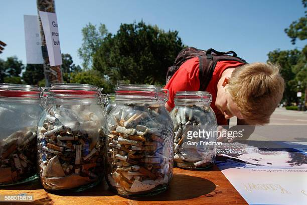 Zak Baron tries to guess how many cigarette butts on Bruin Plaza on the campus of UCLA on April 22 2013 In the foregrond are jars showing 4 weeks of...