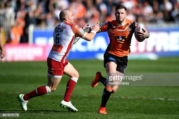 Zak Hardaker of Castleford hands off Luke Walsh of Catalans during the Betfred Super League match between Castleford Tigers and Catalans Dragons at...