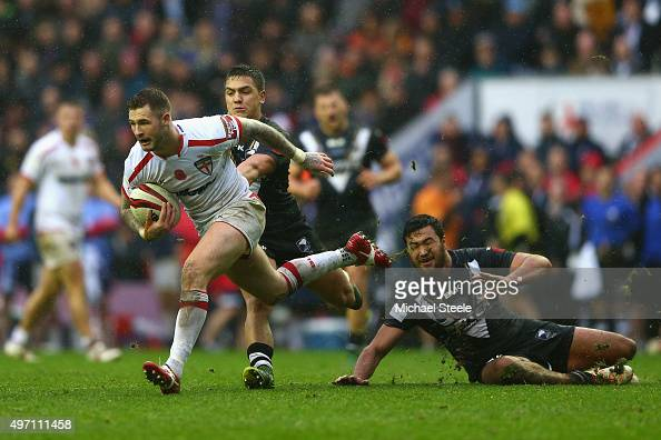 Zak Hardaker of England skips past the challenge of Peta Hiku of New Zealand during the third International Rugby League Test Series match between...