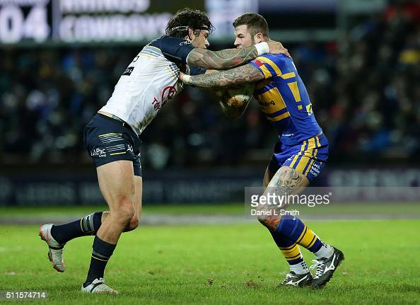 Zak Hardaker of Leeds Rhinos and Ethan Lowe of North Queensland Cowboys tackle hold each other duting a tackle during the World Club Series match...