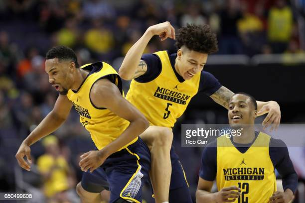 Zak Irvin DJ Wilson and MuhammadAli AbdurRahkman of the Michigan Wolverines celebtrate after Wilson scored in the first half against the Illinois...
