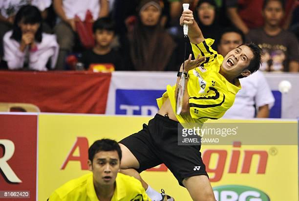 Zakry Abdul Latif smashes the shuttlecock as his teammate Fairuzizuan Mohammd Tazari of Malaysia looks on during their men's double final match of...