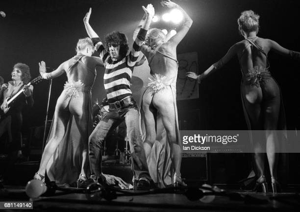 Zal Cleminson and Alex Harvey of The Sensational Alex Harvey Band performing on stage with dancers at New Victoria Theatre London 23 December 1975