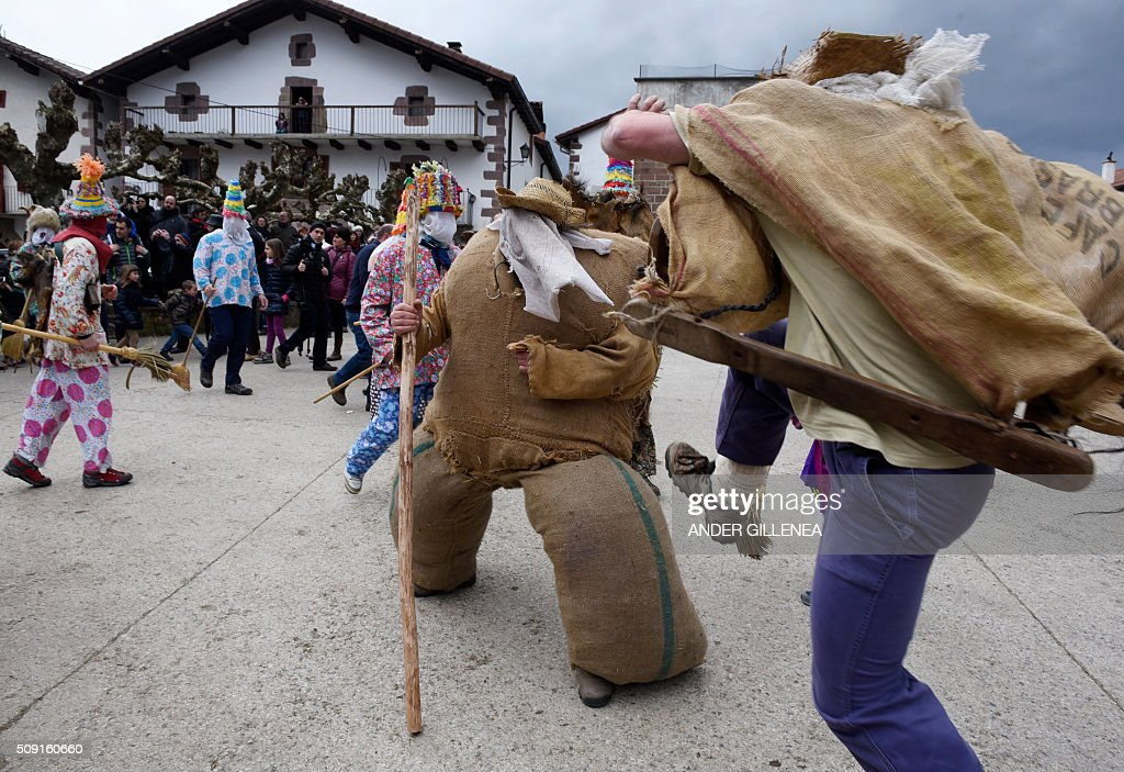 A 'Zaldiko' (man of the horse)(R) kicks Ziripot (C) to make him fall down under the look of 'Txatxoak' during the ancient carnival of Lantz, in the northern Spanish Navarre village of Lantz, on February 9, 2016. / AFP / ANDER GILLENEA
