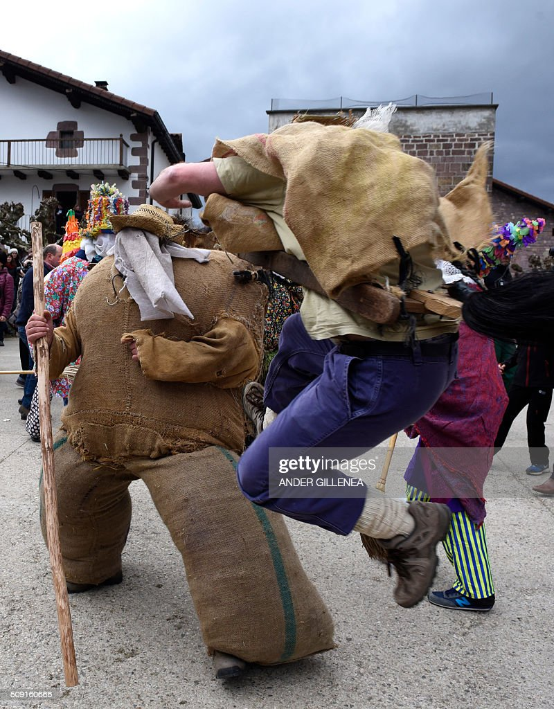 A 'Zaldiko' (man of the horse)(R) kicks Ziripot (L) to make him fall down under the look of 'Txatxoak' during the ancient carnival of Lantz, in the northern Spanish Navarre village of Lantz, on February 9, 2016. / AFP / ANDER GILLENEA