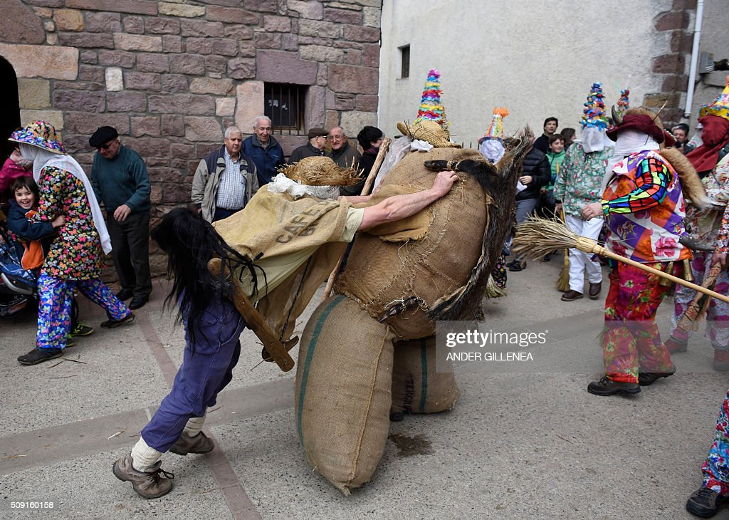 A 'Zaldiko' (man of the horse)(L) pushes Ziripot (C) to make him fall down under the look of 'Txatxoak' during the ancient carnival of Lantz, in the northern Spanish Navarre village of Lantz, on February 9, 2016. / AFP / ANDER GILLENEA