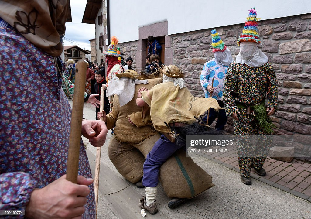 A 'Zaldiko' (man of the horse)(C R) pushes Ziripot (C L) to make him fall down under the look of 'Txatxoak' during the ancient carnival of Lantz, in the northern Spanish Navarre village of Lantz, on February 9, 2016. / AFP / ANDER GILLENEA