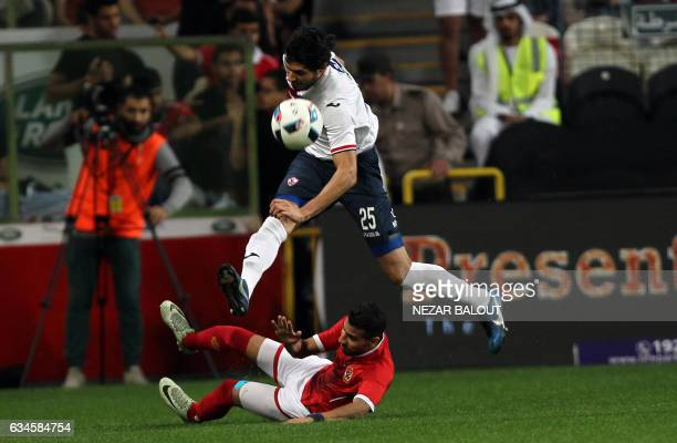 Zamalek's defender Ali Gabr jumps over a tackle by AlAhly's midfielder Moamen Zakaria during the Egyptian Super Cup football match between AlAhly and...