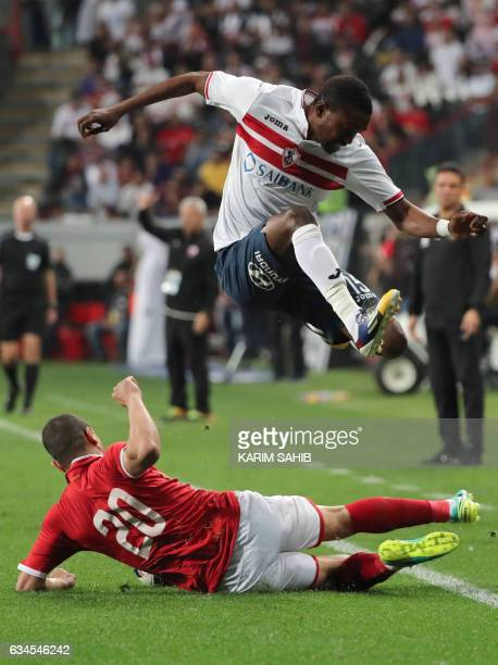 Zamalek's midfielder Maarouf Youssef jumps over a tackle by AlAhly's defender Saad Samir during the Egyptian Super Cup football match between AlAhly...