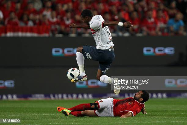 Zamalek's midfielder Maarouf Youssef jumps over a tackly by AlAhly's defender Ahmed Fathy during the Egyptian Super Cup football match between AlAhly...