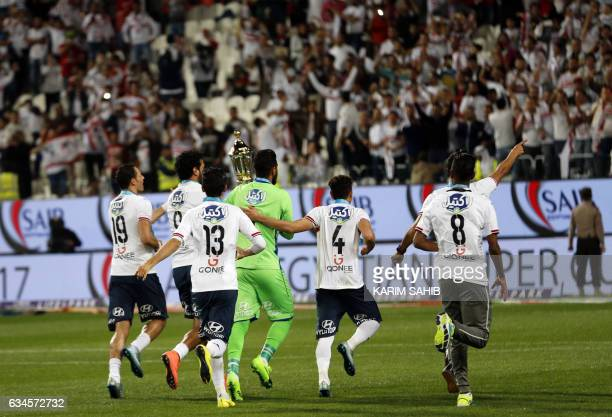 Zamalek's players carry the trophy as they run towards the fans to celebrate their victory in the Egyptian Super Cup football match against AlAhly on...