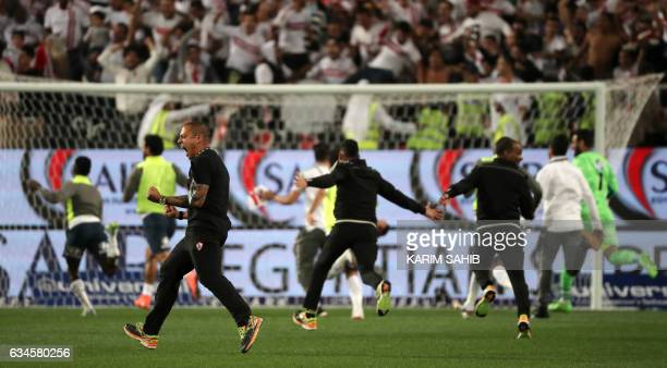 Zamalek's players rush the field to celebrate their victory during the Egyptian Super Cup football match between AlAhly and Zamalek on February 10 at...