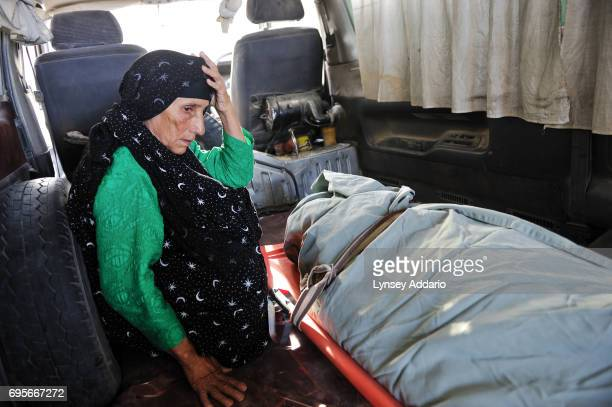 Zamarot sits in an ambulance with the body of her daughter Gul Zada moments after Gul Zada's death in the burn center of the Herat Regional Hospital...