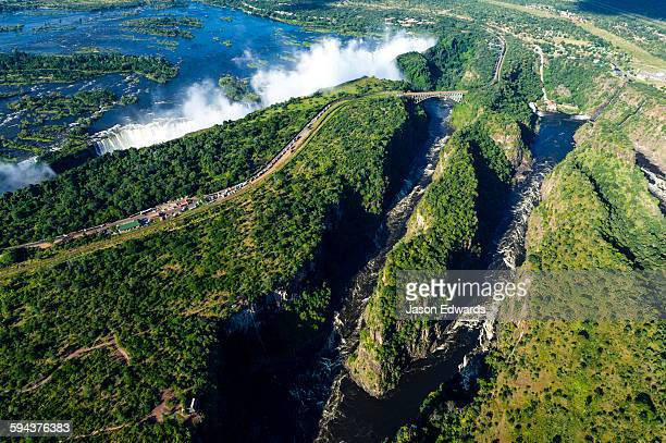 An aerial view of Victoria Falls and a winding gorge carved into a flat plain by the Zambezi River.