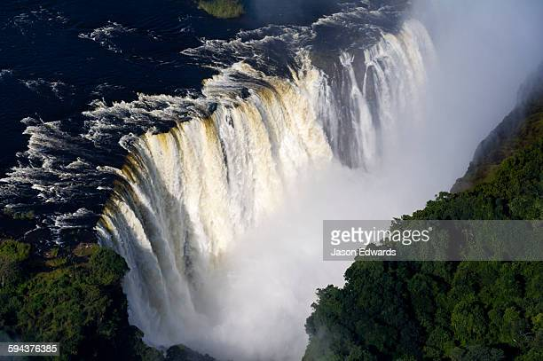 Torrents of water from the Zambezi River cascade over Victoria Falls into the chasm at the Devils Cataract.