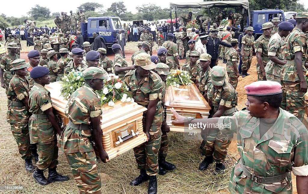 Zambia Army personnel carry the caskets of the victims of the Chibombo bus accident during their burial on February 11, 2013 at Mutengo Cemetery in Ndola. A Zambia bus carrying 74 passengers collided head-on with a heavy goods truck on February 7, near Lusaka killing 53 passengers on board. Zambian President Michael Sata declared three days of national mourning for the victims.
