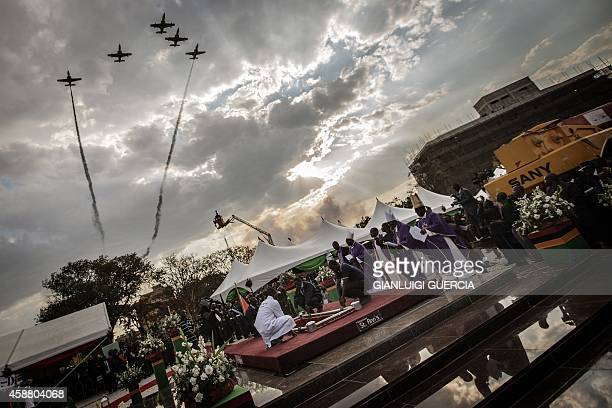 Zambian Air Force jet fighters perform a fly by as the casket with the body of the late Zambian president is lowered into the grave during his state...
