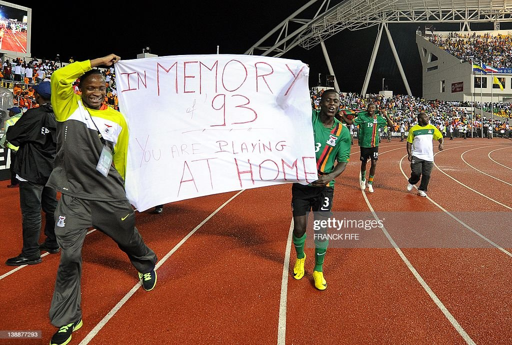 Zambian national football team players celebrate their victory on February 12, 20 at the end of the final match of the 2012 African Cup of Nations (CAN 2012) against Ivory Coat at the stade de l'Amitie in Libreville. Placard refers to February 1993 plane crash that wiped out the Zambian national team off the coast of Gabon.