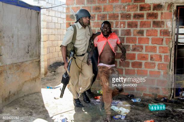 A Zambian Policeman apprehends an alleged looter in the Zingalume Compound where residents have attacked broken and looted foreignrun shops in Lusaka...