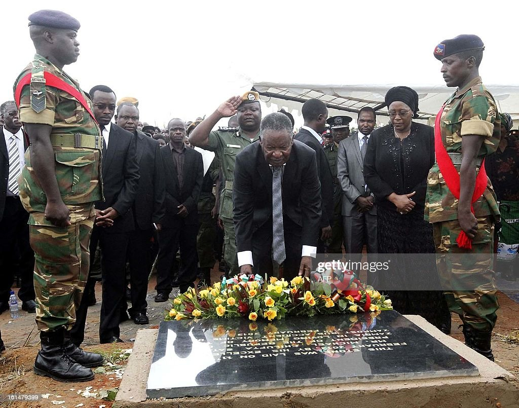 Zambian President Michael Sata (C), flanked by his wife, Dr Christine Kaseba (2ndR), lays a wreath on February 11, 2013 at Mutengo Cemetery in Ndola where the Chibombo accident victims were buried. A Zambia postal service bus carrying 74 passengers collided head-on with a heavy goods truck on February 7, near Lusaka killing 53 passengers on board. President Sata declared three days of national mourning for the victims. AFP PHOTO / JOSEPH MWENDA