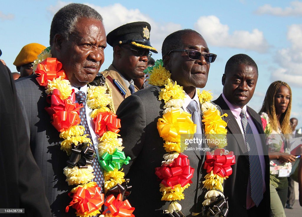 Zambian President <a gi-track='captionPersonalityLinkClicked' href=/galleries/search?phrase=Michael+Sata&family=editorial&specificpeople=1944545 ng-click='$event.stopPropagation()'>Michael Sata</a> (L) is welcomed by Zimbabwean President <a gi-track='captionPersonalityLinkClicked' href=/galleries/search?phrase=Robert+Mugabe&family=editorial&specificpeople=214676 ng-click='$event.stopPropagation()'>Robert Mugabe</a> (R) at the Harare International Airport on April 25, 2012 in Harare, Zimbabwe. Sata is in Zimbabwe for a three day state visit and is expected to officially open the Zimbabwe International Trade Fair on Friday in Bulawayo.