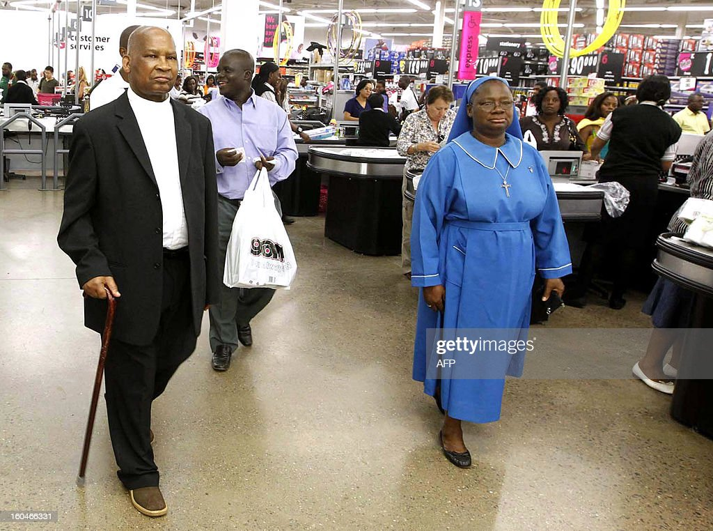 Zambia's Catholic Cardinal Medardo Joseph Mazombwe (L) leaves a supermarket on January 11, 2013 with his assistants Sister Jemana Mushibwe (R) and Father Lazarous Mwansa (C) after he was discharged from Lusaka's Italian Hospital following months of ailment.