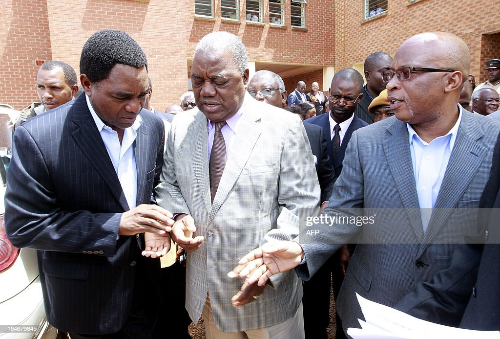 Zambia's ex-president Rupiah Banda (C) chats with former ruling party MMD president Nevers Mumba (R) and opposition United Party for National Development (UPND) leader Hakainde Hichilema outside the Lusaka magistrate court on March 26, 2013 after appearing in court. Banda pleaded not guilty to a charge of abuse of power linked to an oil contract signed while he was in office. He was arrested on March 25, 2013 after being questioned by investigators over his role in a deal with a Nigerian firm.