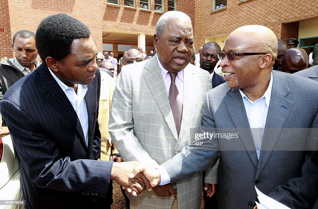 Zambia's ex-president Rupiah Banda (C) stands between former ruling party MMD president Nevers Mumba (R) and opposition United Party for National Development (UPND) leader Hakainde Hichilema outside the Lusaka magistrate court on March 26, 2013 after appearing in court. Banda pleaded not guilty to a charge of abuse of power linked to an oil contract signed while he was in office. He was arrested on March 25, 2013 after being questioned by investigators over his role in a deal with a Nigerian firm.AFP PHOTO/JOSEPH MWENDA