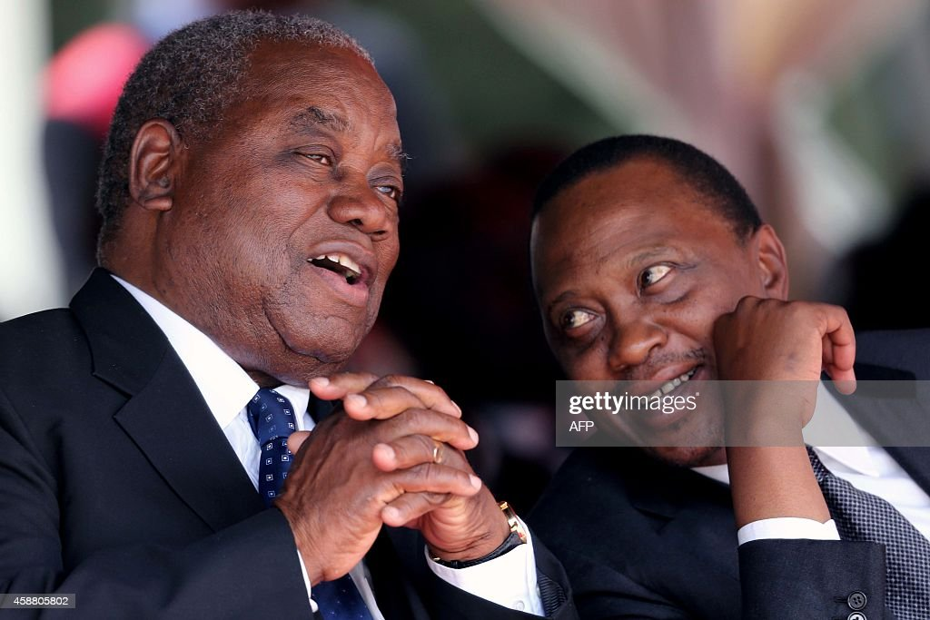 Zambia's former president Rupiah Banda chats with Kenyan President Uhuru Kenyata on November 11 2014 during the funeral of president Michael Sata at...