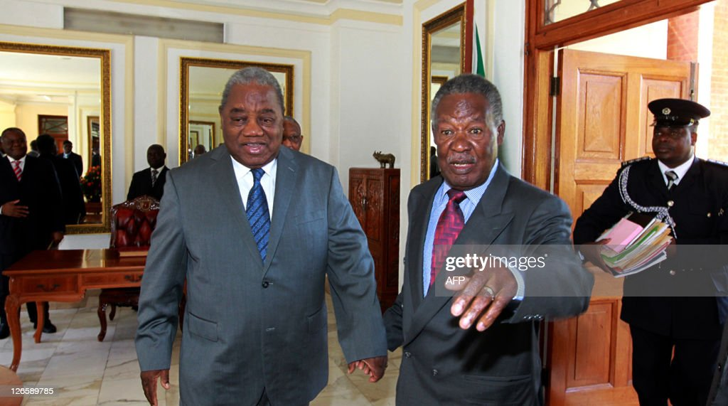 Zambia's Former President Rupiah Banda holds hands with his successor Michael Sata at the State House in Lusaka on September 26 2011 Sata was sworn...