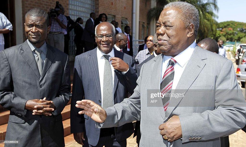 Zambia's former President Rupiah Banda waves to supporters next to his Communication advisor Kennedy Limwanya and Joe Mwale as he leaves Lusaka's...