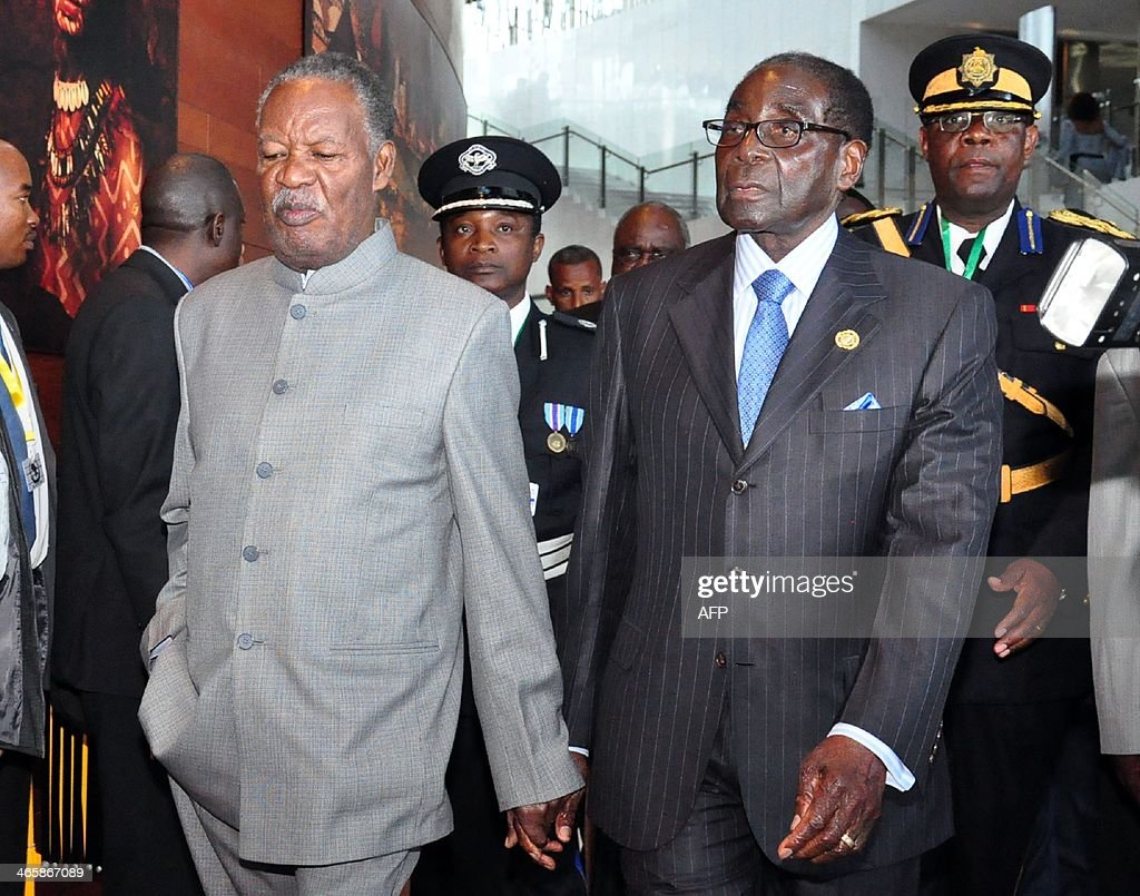 Zambia's President <a gi-track='captionPersonalityLinkClicked' href=/galleries/search?phrase=Michael+Sata&family=editorial&specificpeople=1944545 ng-click='$event.stopPropagation()'>Michael Sata</a> (L) and his Zimbabwean counterpart President Robert Mugabe walk hand in hand on January 30, 2014 as they arrive at the African Union (AU) headquarters in Addis Ababa. Mohamed Ould Abdel Aziz took over as African Union chairman on Thursday, replacing Ethiopian Prime Minister Hailemariam Desalegn in the one-year post. Aziz, in his opening speech, congratulated Hailemairan 'for the remarkable work accomplished during his tenure,' adding that 'he has contributed brilliantly to strengthen the role of Africa on both continental and international levels'. AFP PHOTO/Samuel GEBRU