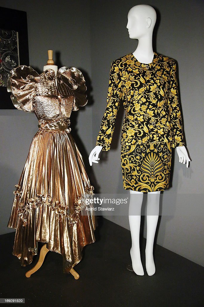 A Zandra Rhodes gold lame dress, circa 1981 is shown next to a Gianni Versace suit, circa 1992 at the RetroSpective Press Preview at The Museum at FIT on May 22, 2013 in New York City.
