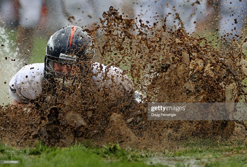 Zane Beadles of the Denver Broncos dives into the mud as rookies partake in the slip and slide fumble drill during training camp at Dove Valley on...