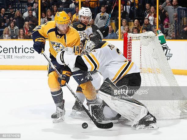 Zane McIntyre of the Boston Bruins battles outside the crease against Mattias Ekholm of the Nashville Predators during an NHL game at Bridgestone...
