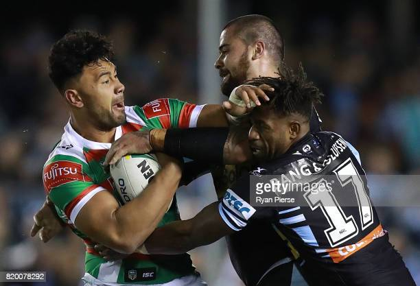 Zane Musgrove of the Rabbitohs is tackled by James Segeyaro and Andrew Fifita of the Sharks during the round 20 NRL match between the Cronulla Sharks...