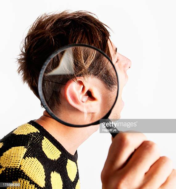 Zany young man with magnifying glass over ear