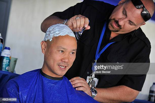 Zapposcom CEO Tony Hsieh has his head shaved by Loren Becker before the unveiling of the 'ShoeZaphone' during the annual Bald and Blue fundraiser at...
