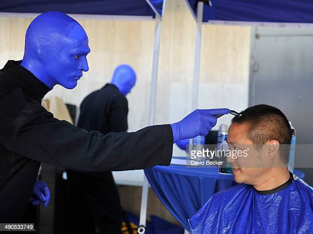 Zapposcom CEO Tony Hsieh pretends to have his head shaved by a member of Blue Man Group before the unveiling of the 'ShoeZaphone' during the annual...