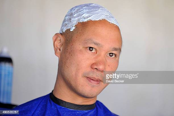 Zapposcom CEO Tony Hsieh's head is prepped with shaving cream before being shaved during the annual Bald and Blue fundraiser at Zappos headquaters on...