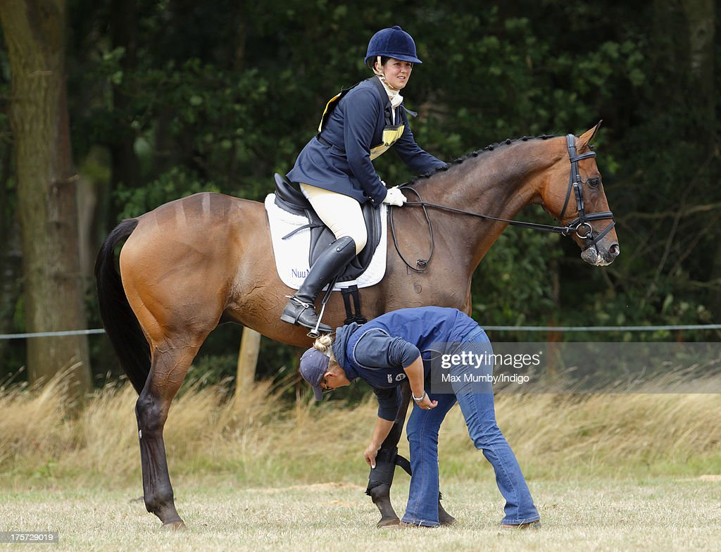 Zara Phillips prepares her horse on which rider Aimee Aspinall is competing at the Smiths Lawn Horse Trials on August 5, 2013 in Windsor, England.