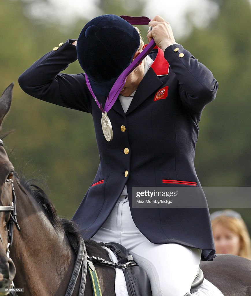 Zara Phillips puts on her London 2012 Olympic silver medal before she and her fellow team eventing medal winners parade at the Blenheim Palace International Horse Trials on September 9, 2012 in Woodstock, England.
