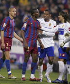 Zaragoza players try to persuade Samuel Eto'o of Barcelona from abandoning the Primera Liga match against Real Zaragoza after some Zaragoza fans made...