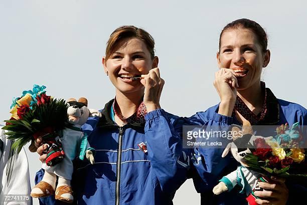 Zarrina Ganieva and Sevara Ganiyeva of Team Uzbekistan bite their Gold Medal in the Women's Lightweight Double Sculls Rowing Competition during the...