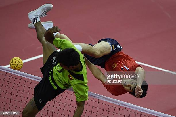 Zaw Aung Zaw of Myanmar jumps for the ball against Kim YoungMan of South Korea during their Sepaktakraw men's double final game during the 2014...