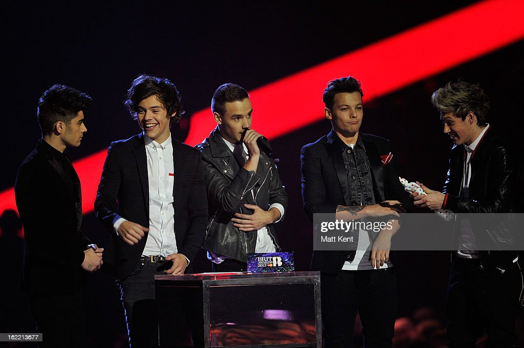 Zayn Malik, Harry Styles, Liam Payne, Louis Tomlinson, and Niall Horan of One Direction congratulate each other before receiving the Brits Global Success Award on stage during the Brit Awards 2013 at the 02 Arena on February 20, 2013 in London, England.