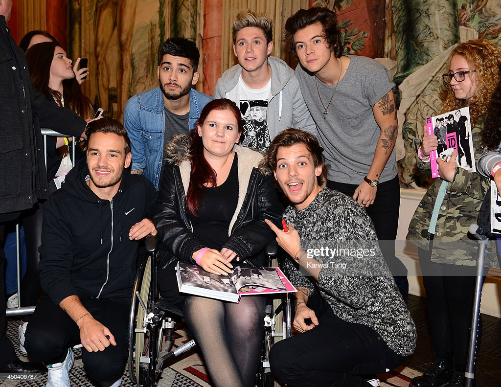 Zayn Malik, Liam Payne, Louis Tomlinson, Niall Horan and Harry Styles of One Direction pose with fans as they attend the book signing of One Direction's new book 'Where We Are' held at Alexandra Palace on November 18, 2013 in London, England.