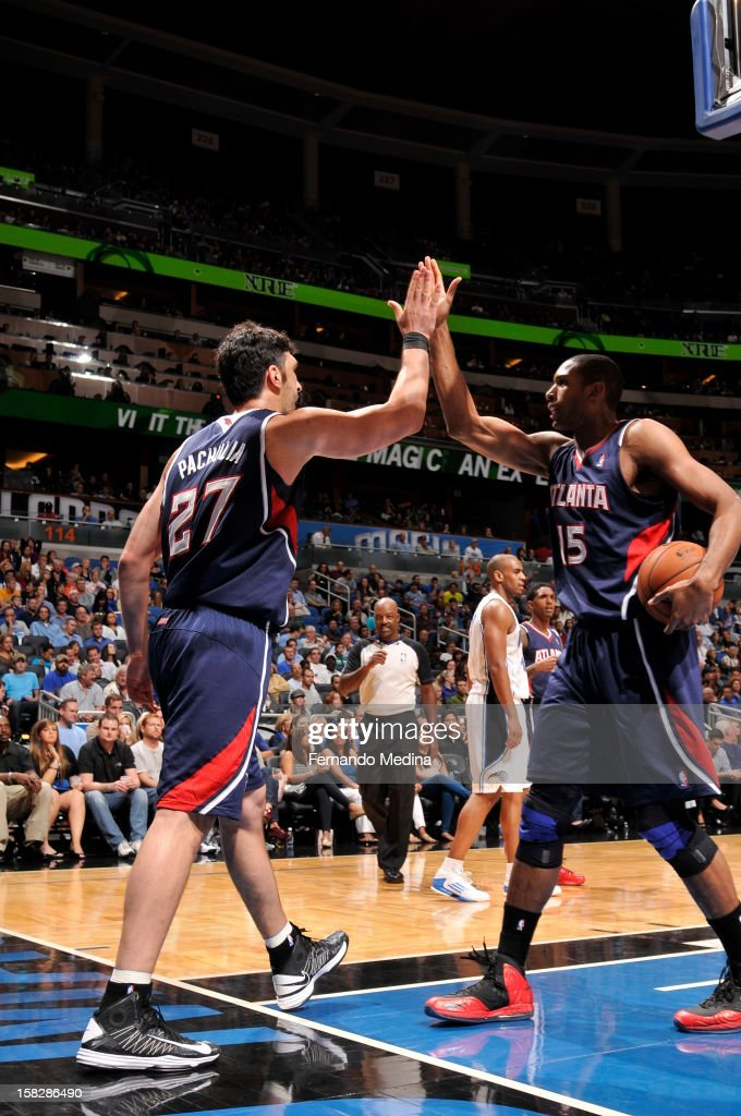 Zaza Pachulia #27 and Al Horford #15 of the Atlanta Hawks give eachother a high five against the Orlando Magic during the game on December 12, 2012 at Amway Center in Orlando, Florida.