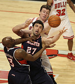 Zaza Pachulia and Damien Wilkins of the Atlanta Hawks try to control the ball in front of Omer Asik of the Chicago Bulls at the United Center on...