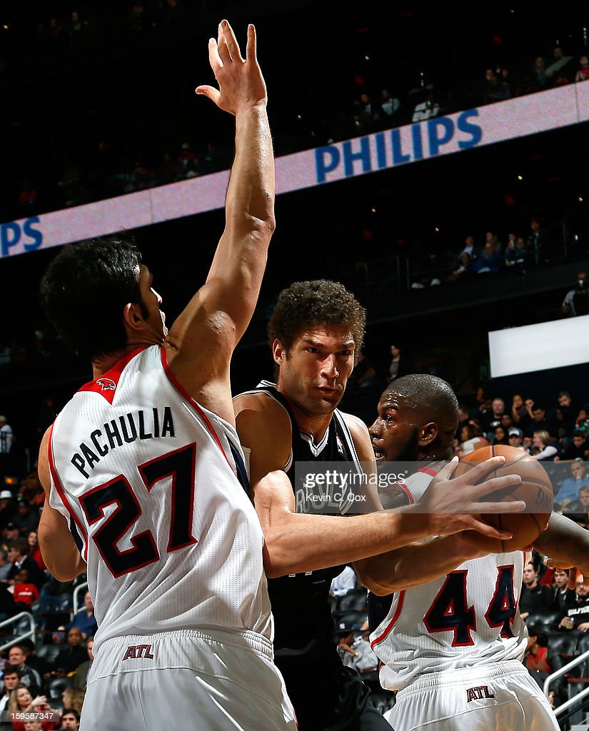 Zaza Pachulia #27 and Ivan Johnson #44 of the Atlanta Hawks defend against Brook Lopez #11 of the Brooklyn Nets at Philips Arena on January 16, 2013 in Atlanta, Georgia.